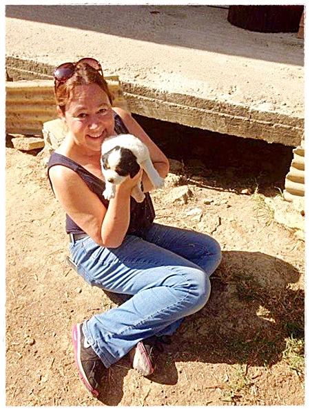 deze vrijwilliger laat trots de pup zien die zij uit het riool heeft gered